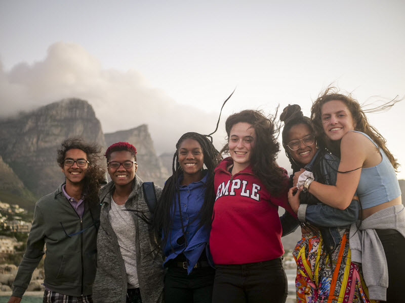 Six students outside at a mountain on the coast