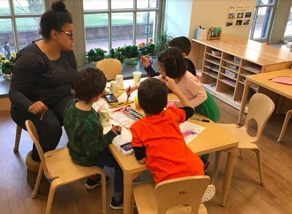 teacher at small table leading watercolor painting with young students
