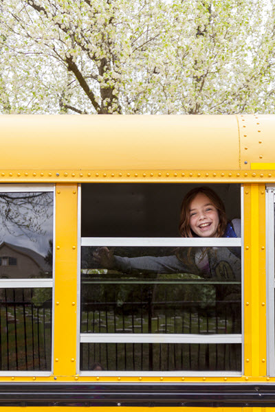 child on school bus smiling