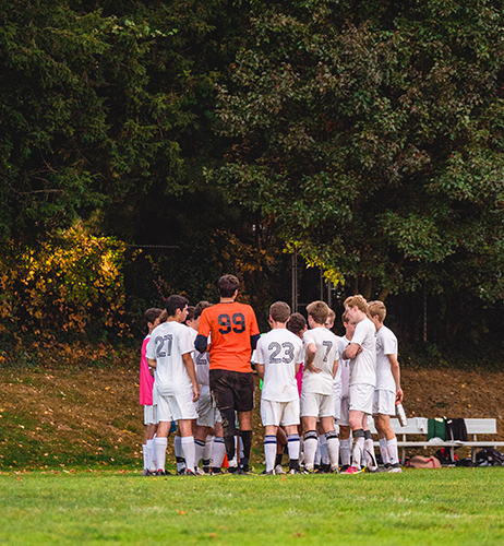 Boys soccer team standing in a huddle